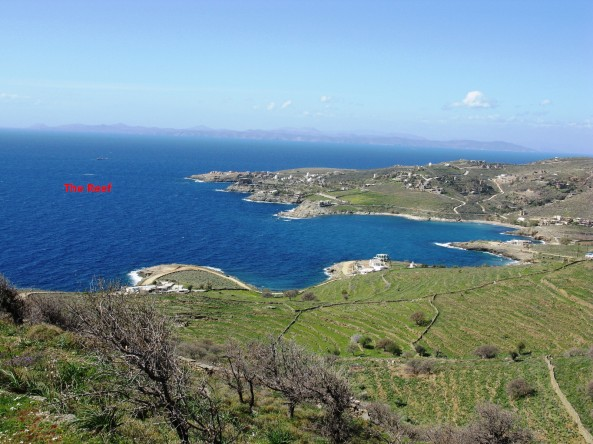 View of Koundouros Bay (a.k.a. Aghios Emilianos, Kavia Bay) from the Katevati spring (+150 meters). Makronisos and mainland Attica visible in the background. Also visible is the light white surf of the reef on the left open water section.