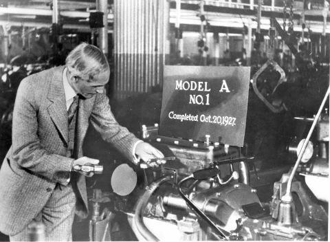 Henry Ford punches the engine number on the first Ford Model A off the assembly line.