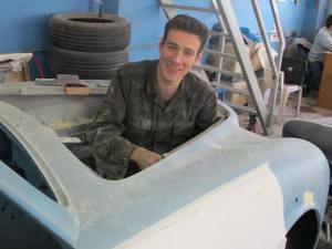A young assistant is positioned in the engine bay, sanding and doing preparatory tasks